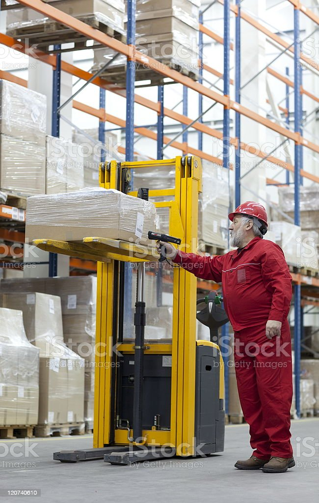 Senior worker with bar code reader in warehouse royalty-free stock photo