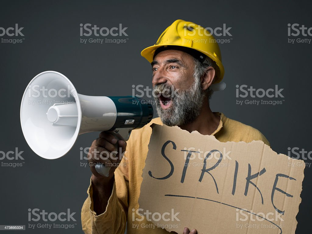 Senior Worker With Hardhat Shouting With Megaphone, Holding Strike Placard stock photo