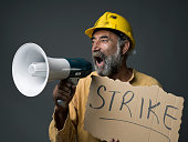 Senior Worker With Hardhat Shouting On Megaphone, Holding Strike Placard