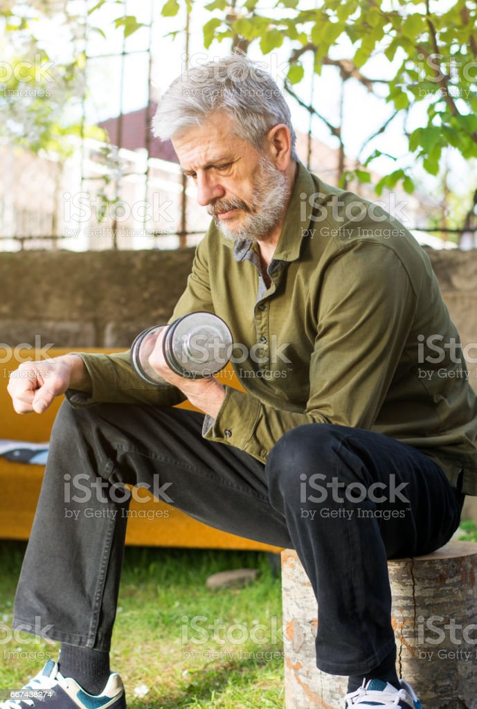 Senior working out with dumbbell outdoors stock photo