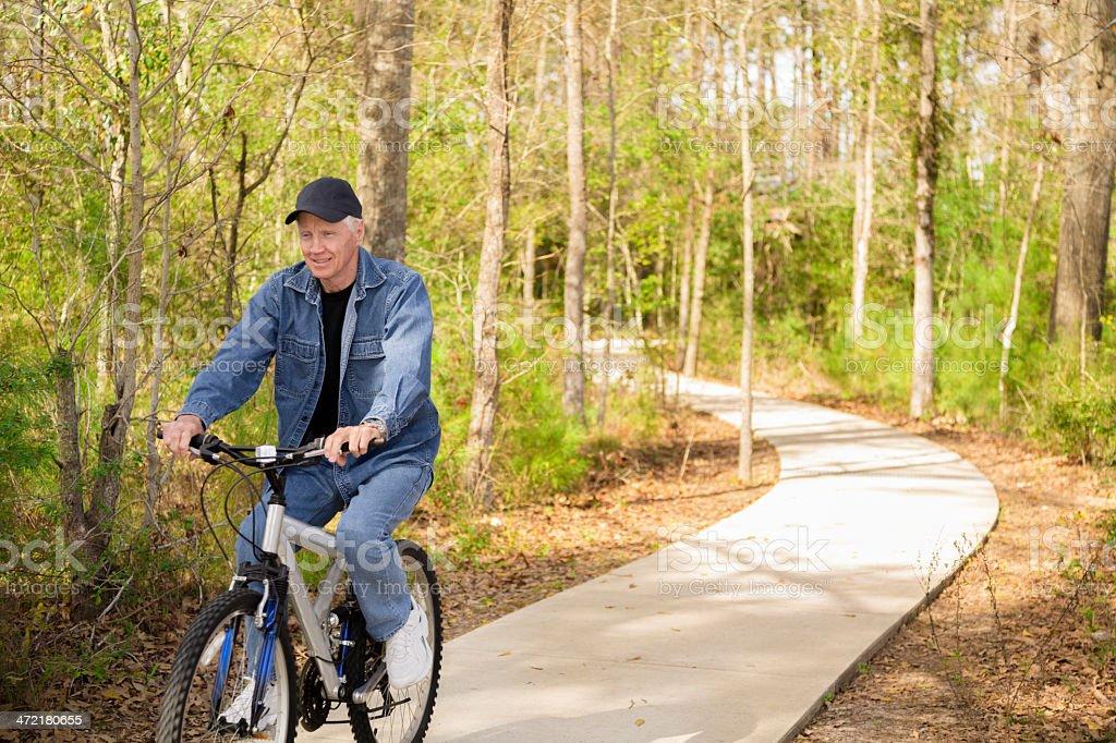 Seniors: Active senior man outdoors riding his bike. Nature. royalty-free stock photo