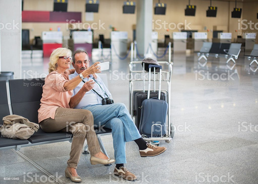 Seniors ar airport taking a selfie stock photo