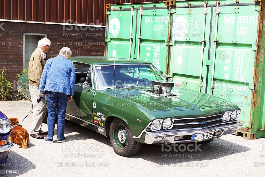 Seniors are watching green US muscle car stock photo
