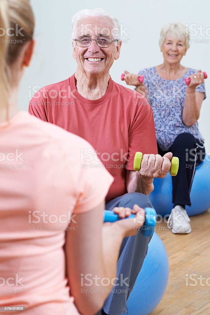 Seniors At Fitness Class With Instructor stock photo