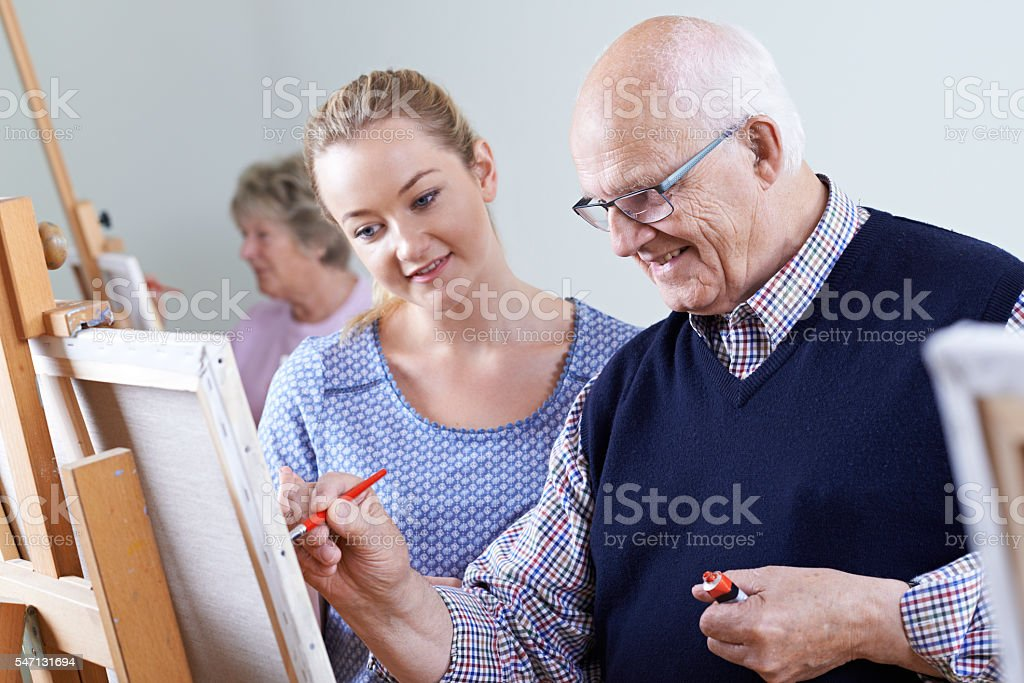 Seniors Attending Painting Class With Teacher stock photo