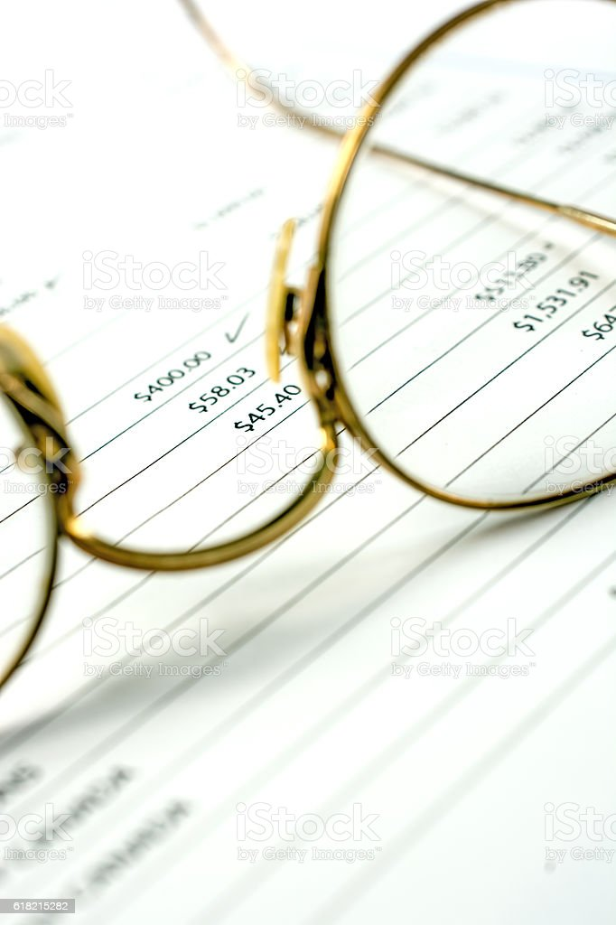 Seniors bank statement with old pair of glasses upon it stock photo