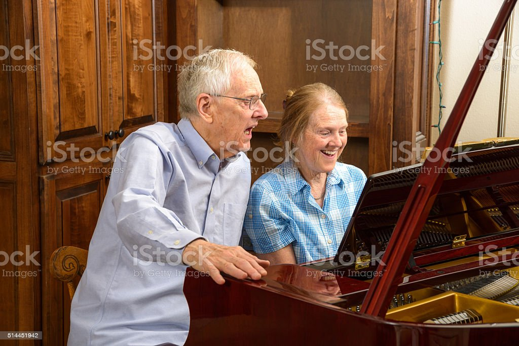 Seniors, brother, sister enjoying vocal and piano music together stock photo