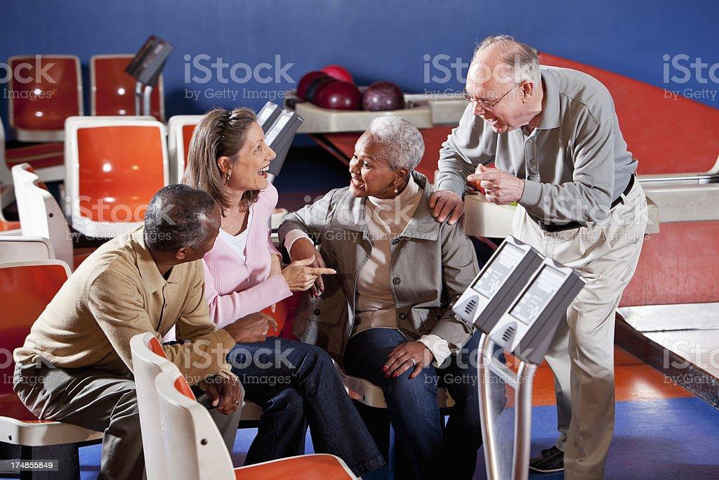 Seniors chatting at bowling alley stock photo