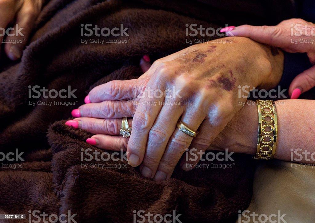 Seniors clasp hands stock photo