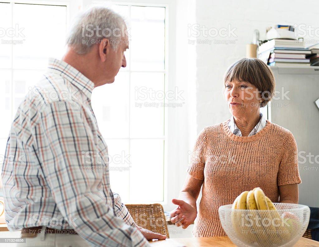 Seniors couple talking on a kitchen royalty-free stock photo