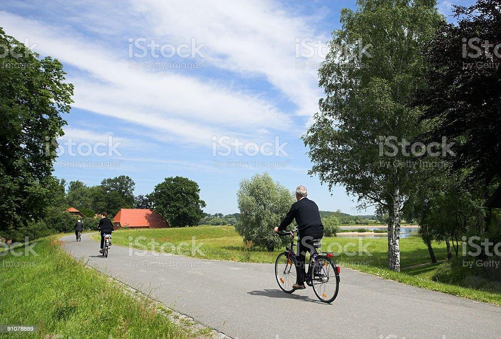 Seniors cycling countryside on dyke royalty-free stock photo