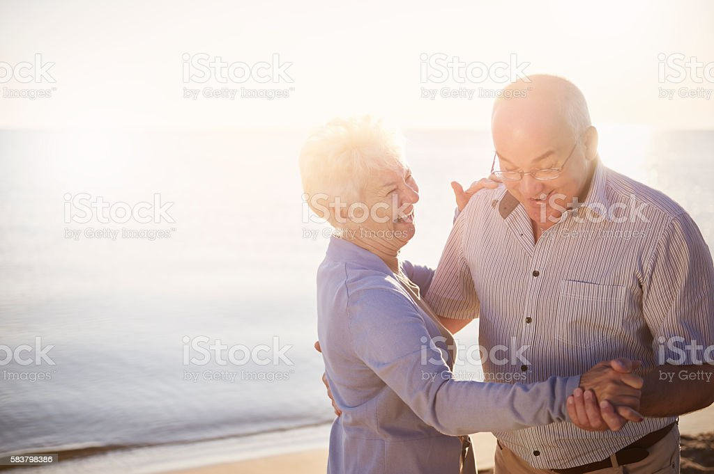 Seniors dancing on the beach on the sunrise stock photo