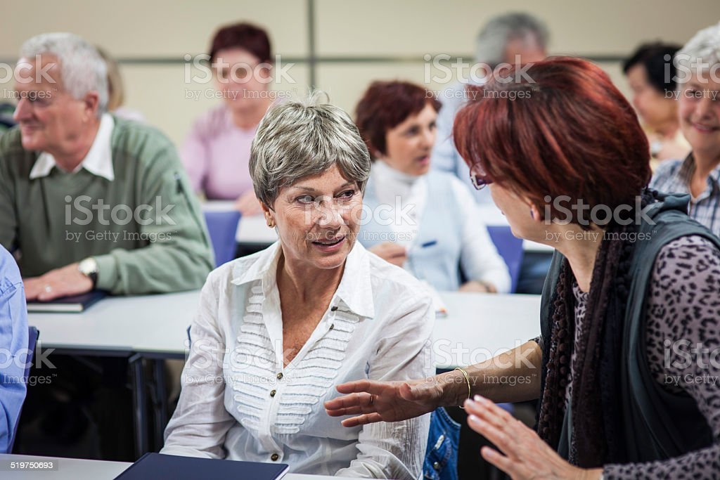 Seniors Enjoying Conversation In Community Center stock photo