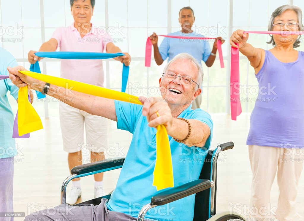 Seniors exercising with exercise bands in fitness class royalty-free stock photo