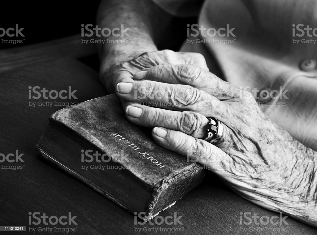 Senior's hands on old Bible royalty-free stock photo