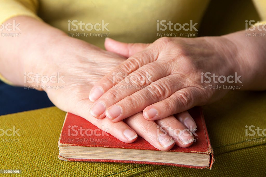 Senior's hands on old book stock photo