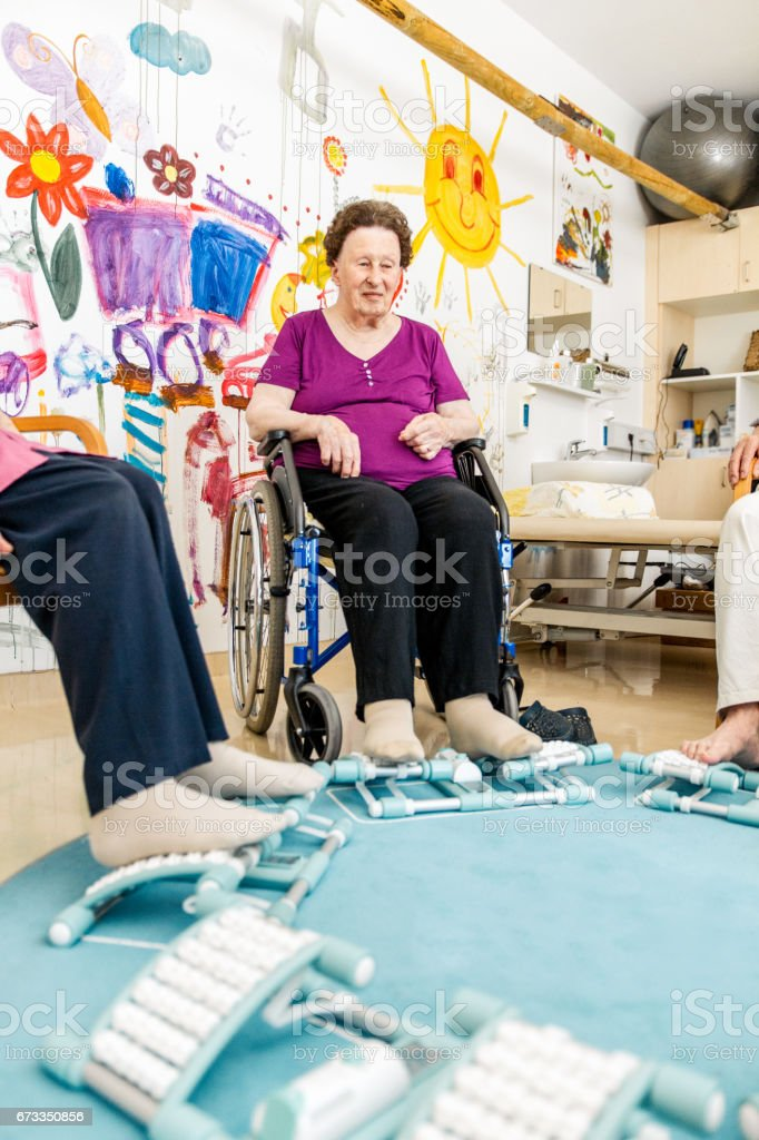 Seniors Having Foot Massage With Foot Roller In The Retirement Home - Close Up stock photo