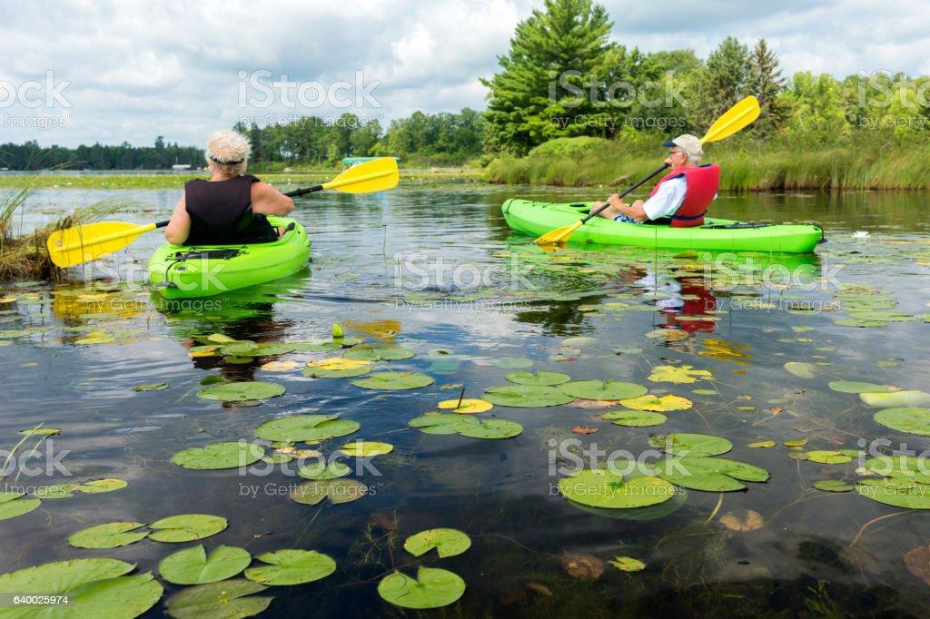 Seniors kayaking in lake stock photo