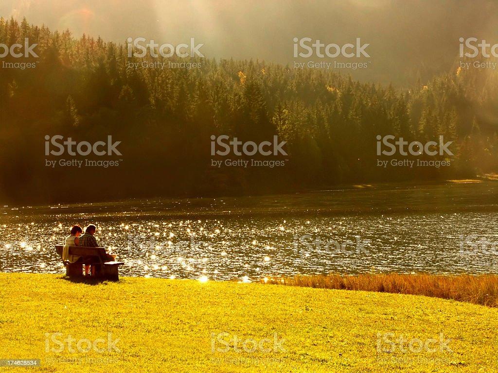 seniors make pause on lake at sunset stock photo