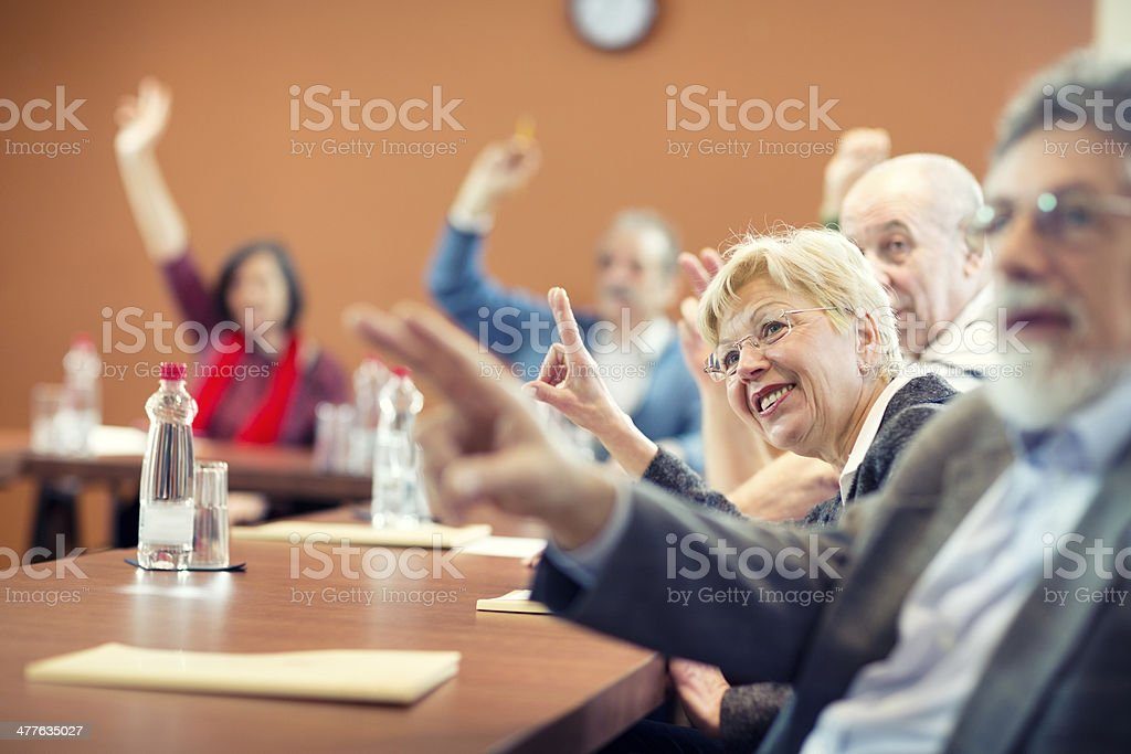 Seniors on seminar raising hands stock photo