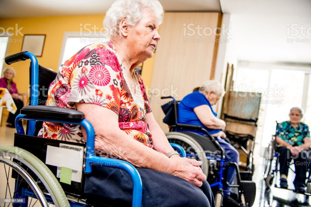 Seniors On The Wheelchair Attend In The Retirement Home stock photo