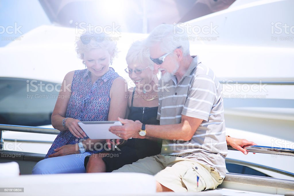 Seniors on vacation on Yacht using digital tablet stock photo