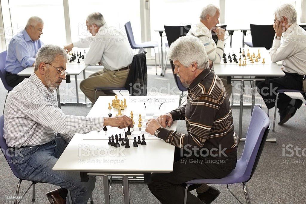 Seniors playing chess in community center stock photo