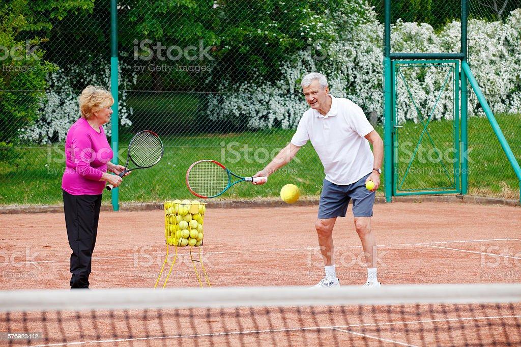Seniors playing tennis stock photo