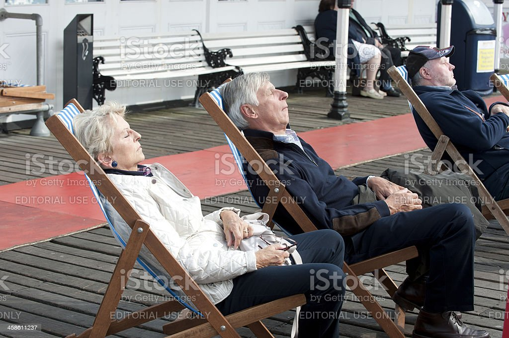 Seniors Sleeping in Deck Chairs on Brighton Pier royalty-free stock photo