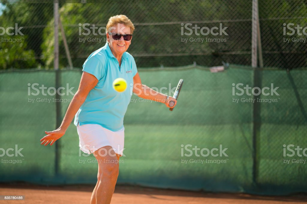 Seniors Taking on the World, happy fit 70 years old woman playing tennis stock photo