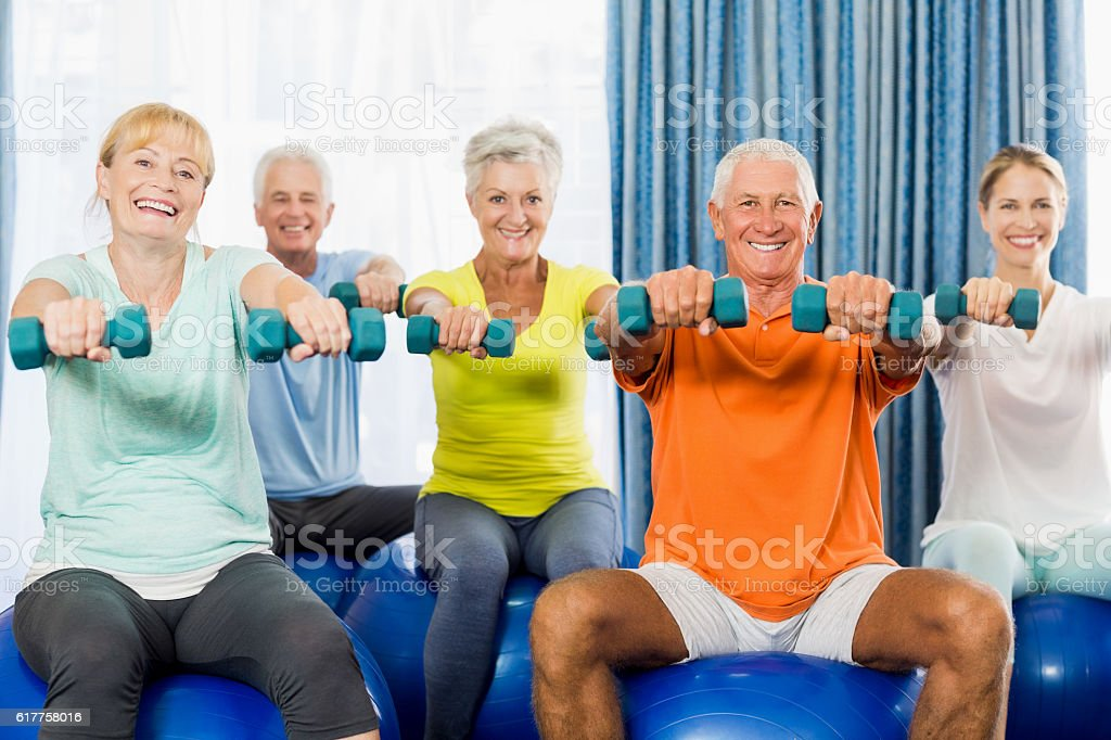 Seniors using exercise ball and weights stock photo