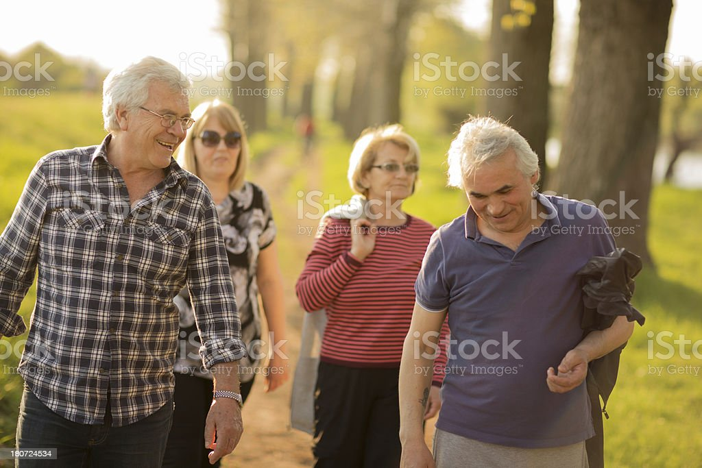 Seniors walking outdoors stock photo