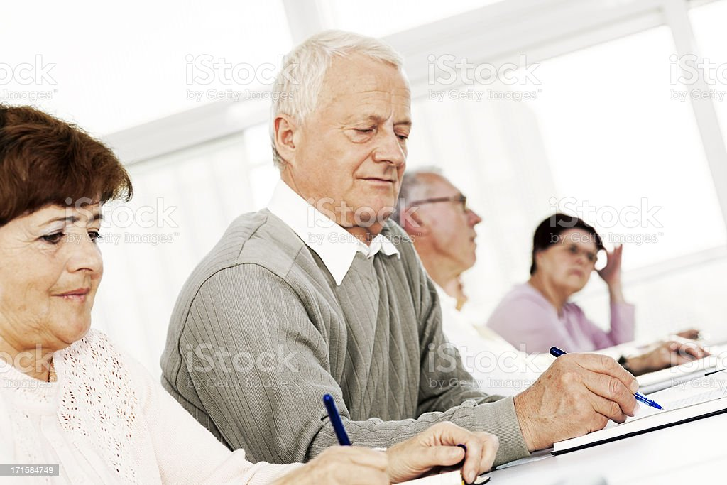 Seniors Writing Notes at Lecture Hour royalty-free stock photo