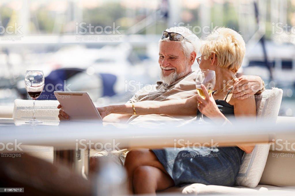 Seniour couple using digital tablet on a yacht stock photo