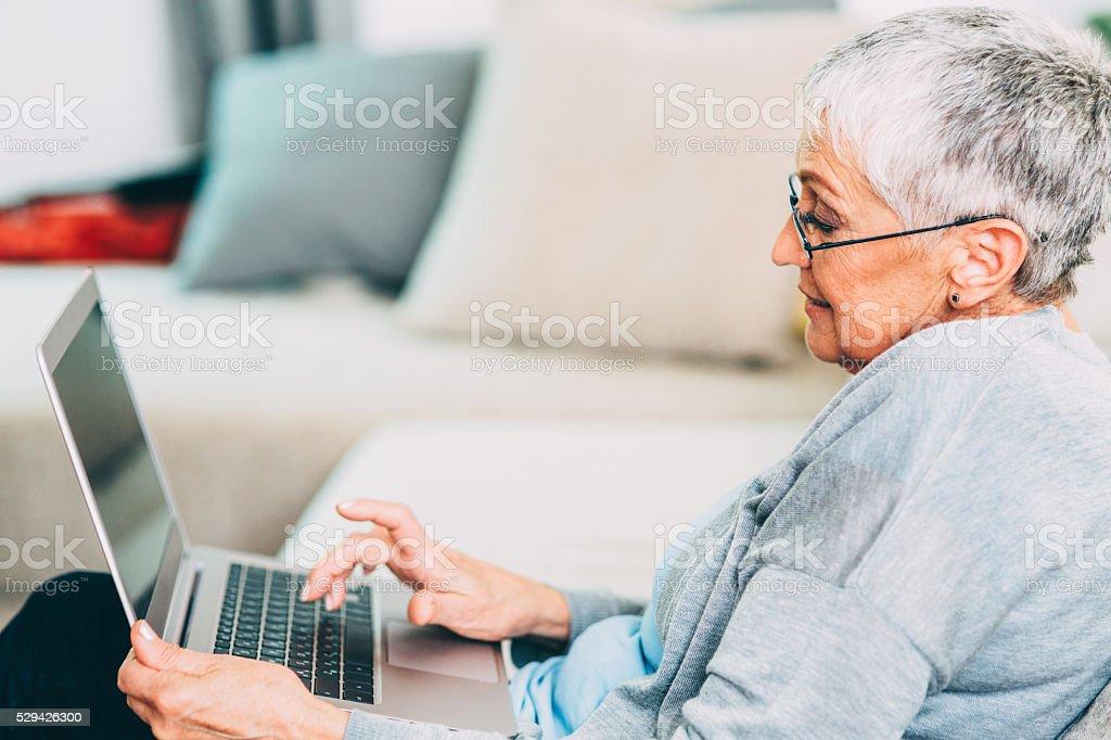 Seniour woman using new technology stock photo