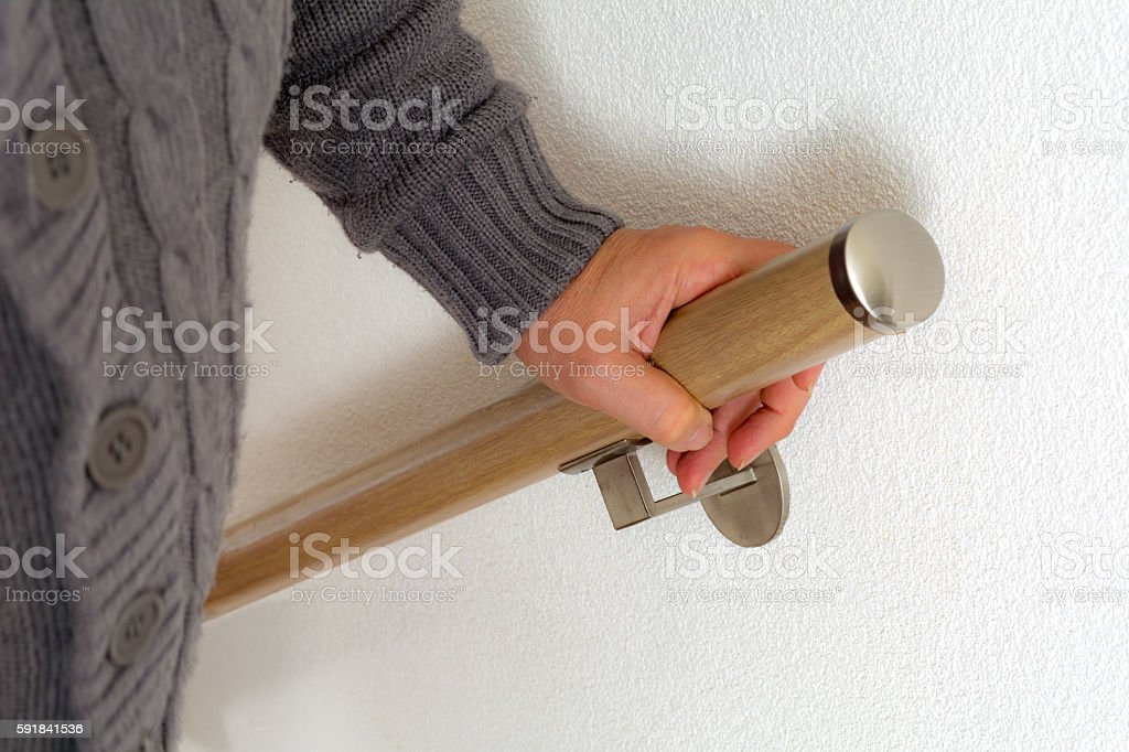 senoir holding on to handrail going up the stairs stock photo