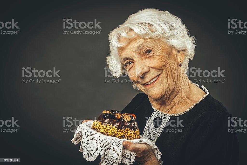 Senoir lady holding cake stock photo