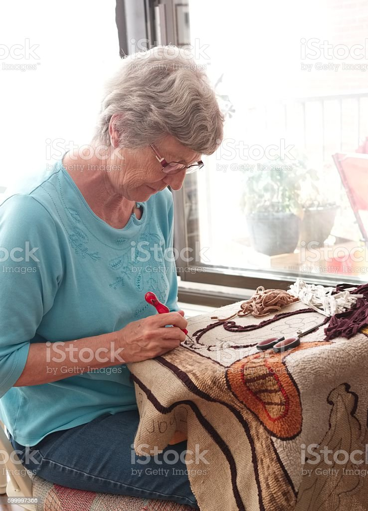 Senoir woman hooking a rug. stock photo