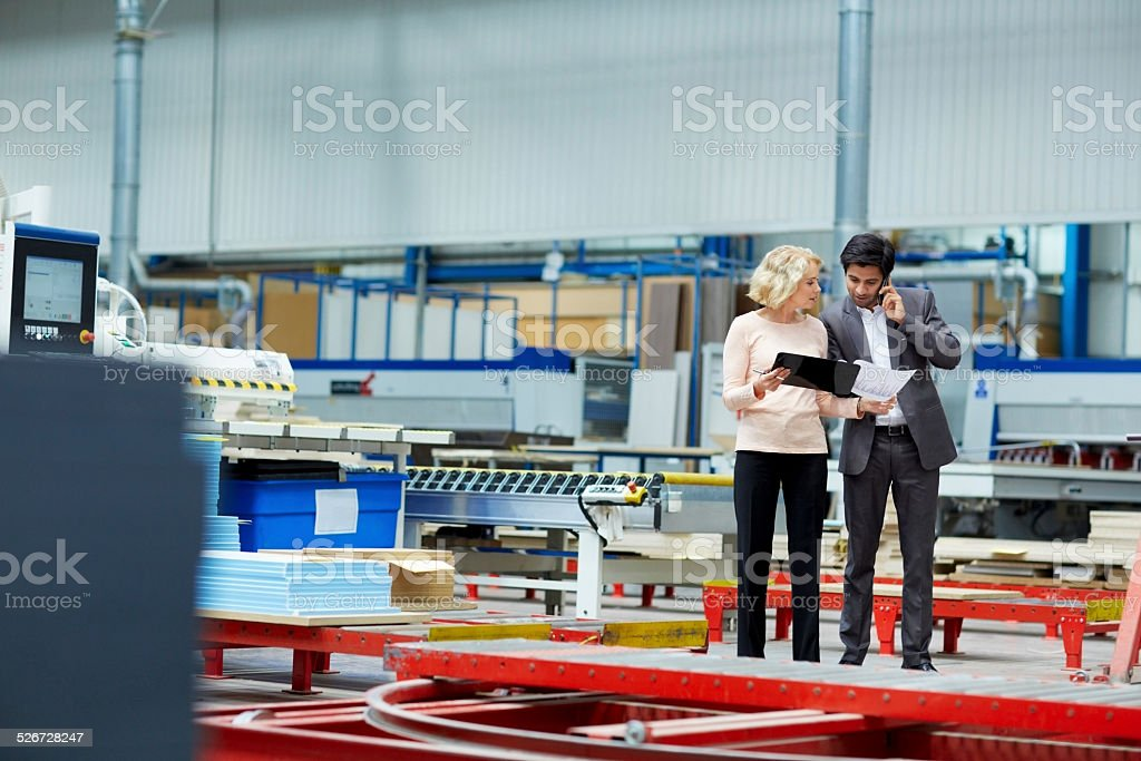 Senor woman showing production reports to manager stock photo