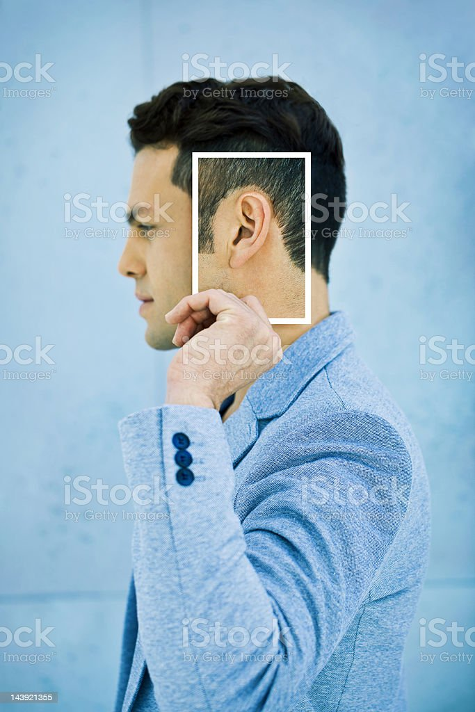 Senses: Man holding a photo of his ear stock photo