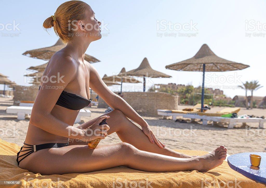 Sensous slim woman applying suntan oil stock photo