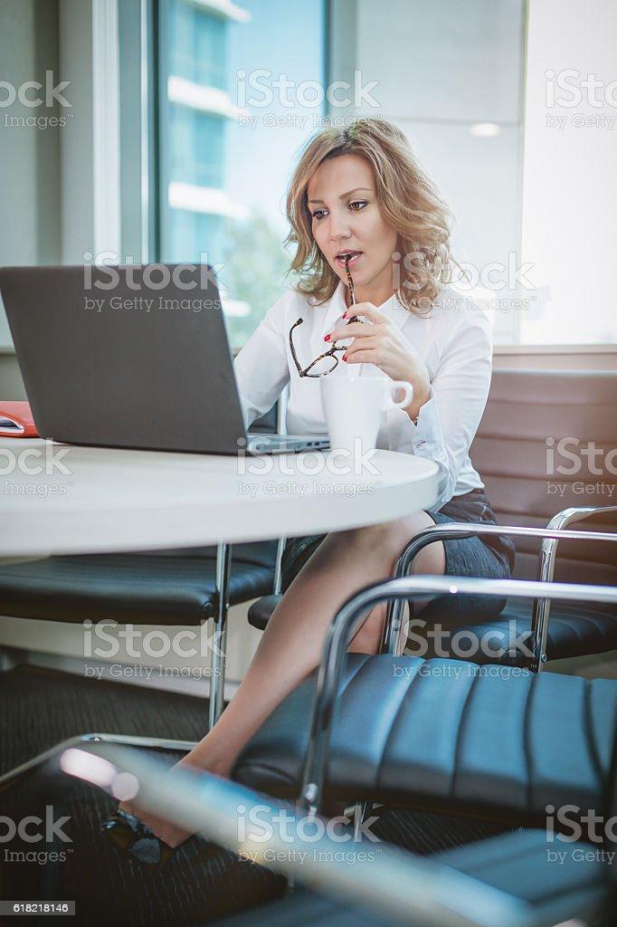 sensual businesswoman biting glasses and working stock photo