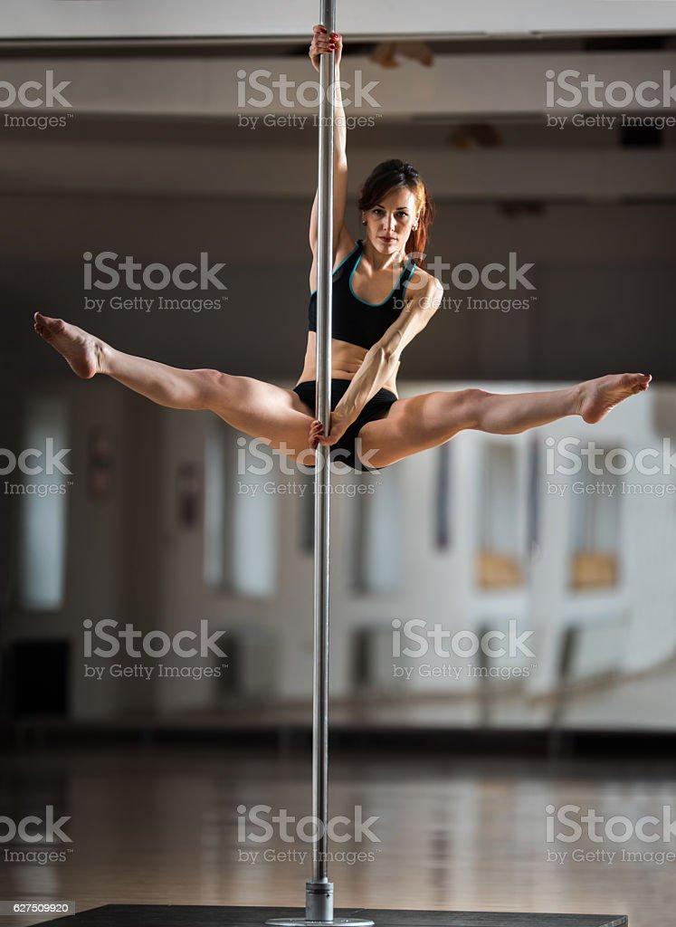Sensual dancer exercising pole dancing in a studio. stock photo