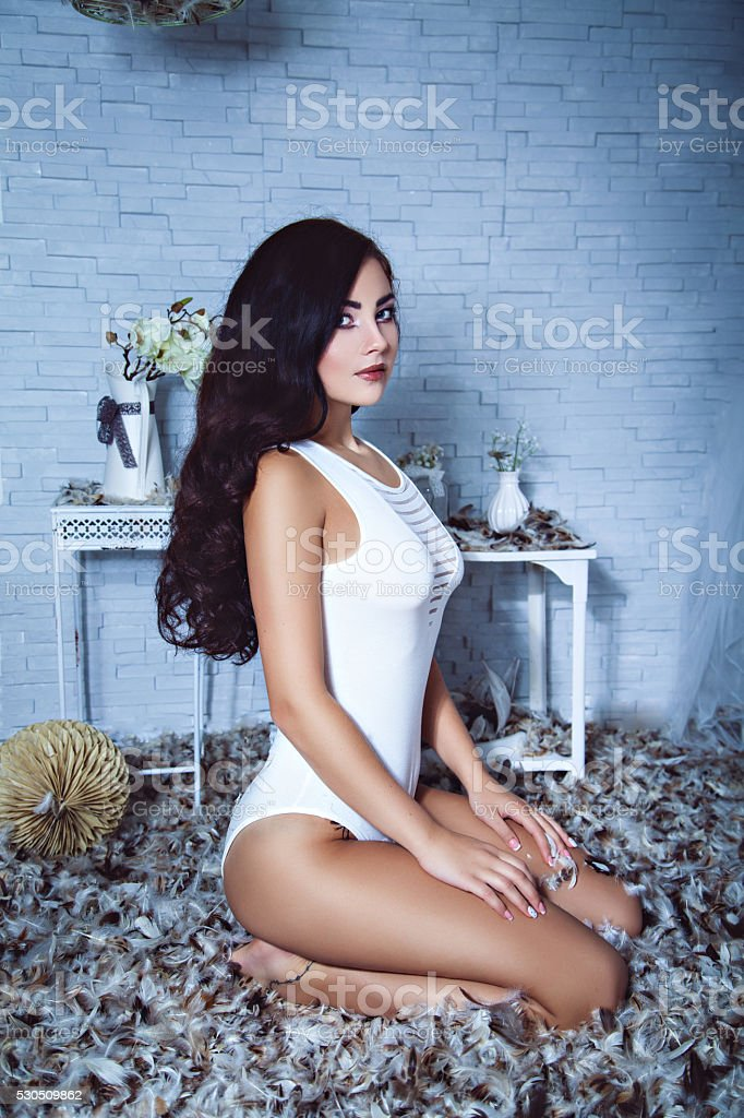 Sensual girl in feathers room stock photo