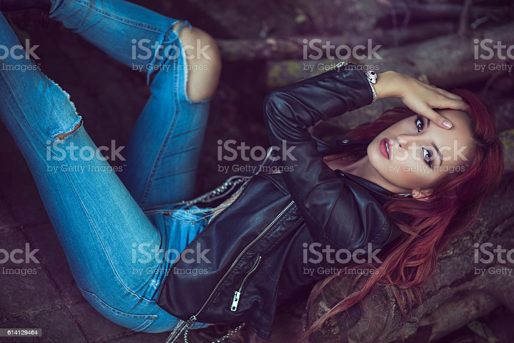 Sensual Redhead Laying on Trees with Unzipped Leather Jacket stock photo