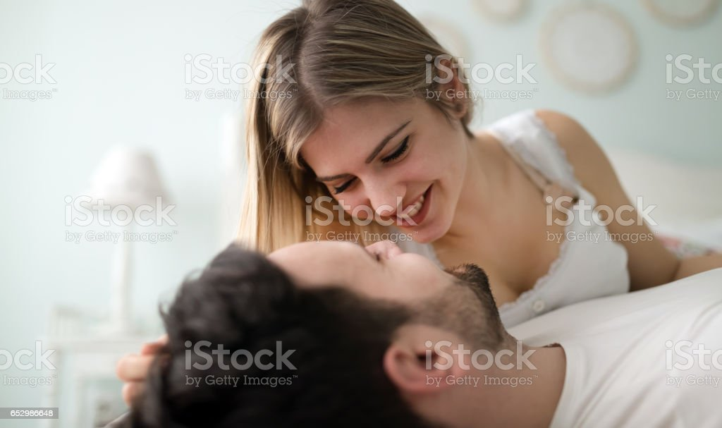 Sensual romantic foreplay by couple in love in bed stock photo