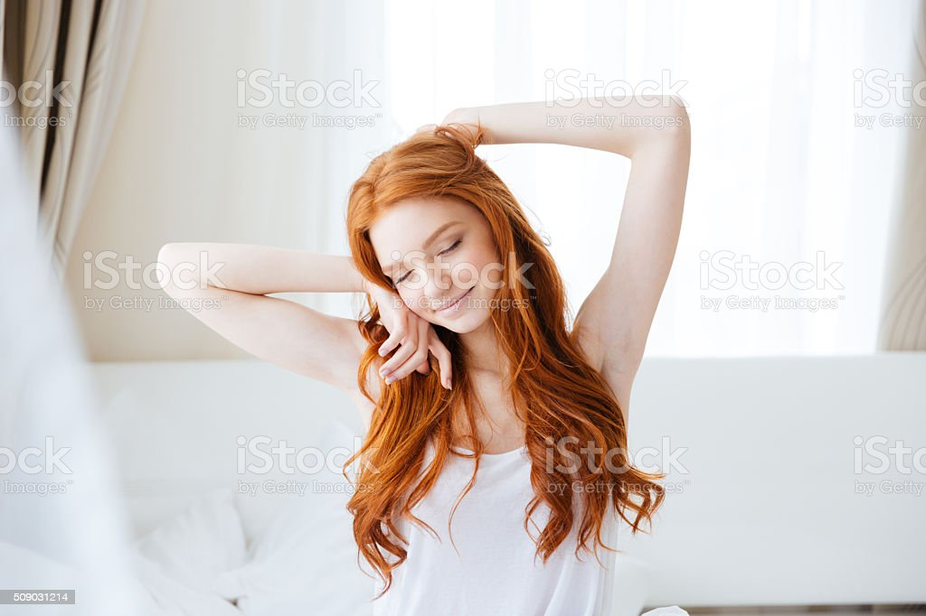 Sensual smiling woman sitting and stretching in bed stock photo