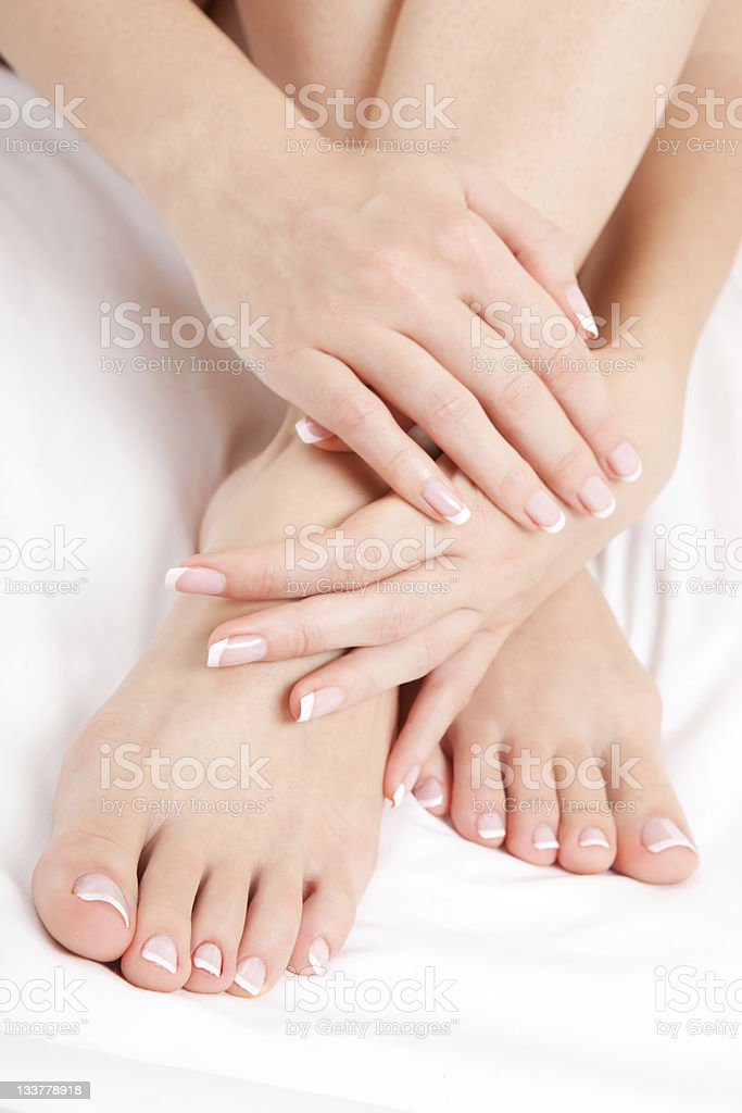 A sensual view of woman's manicured hands and feet stock photo