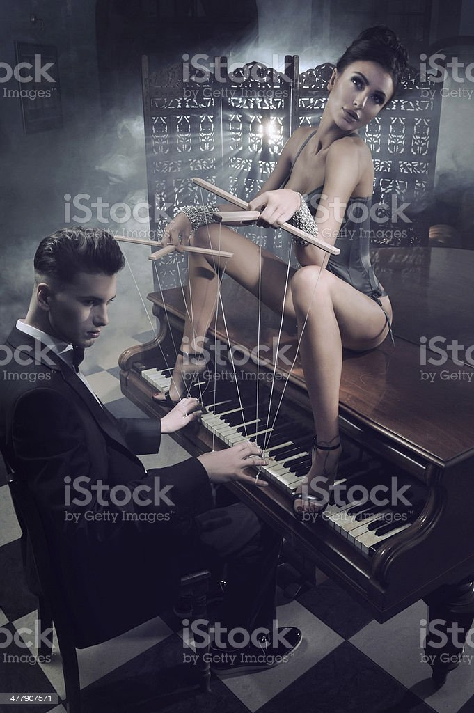 Sensual woman in sexy lingerie sitting on a piano royalty-free stock photo