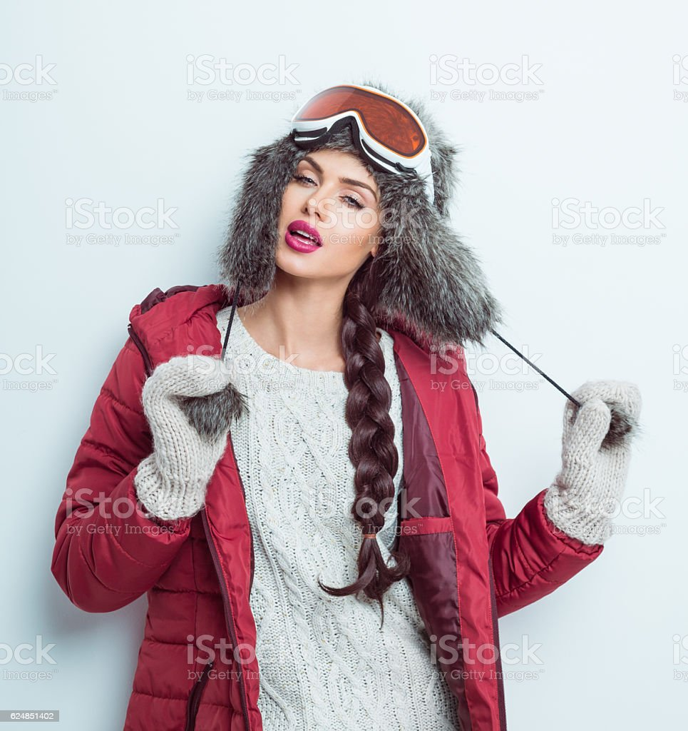 Sensual woman in winter outfit - puffer jacket, fur hat stock photo